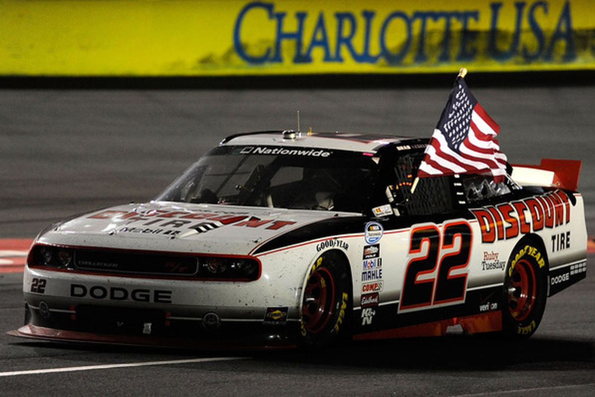 Brad Keselowski celebrates by waving the American flag on track after winning the NASCAR Nationwide Series Dollar General 300 at Charlotte Motor Speedway. (Photo: John Harrelson/Getty Images for NASCAR)