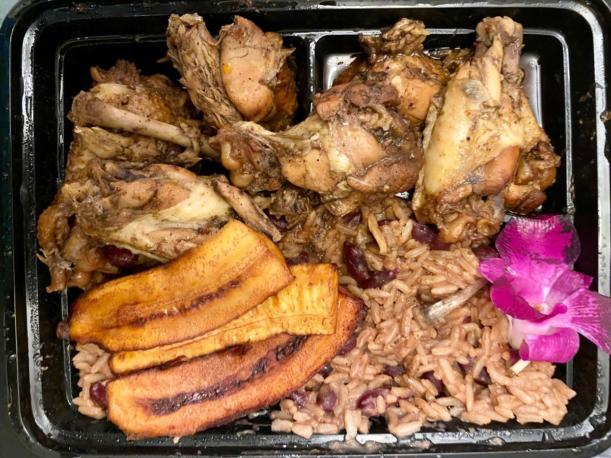 Takeout container with several pieces of jerk chicken wings and drummettes, pelau rice, and fried plantains, with a purple flower as garnish
