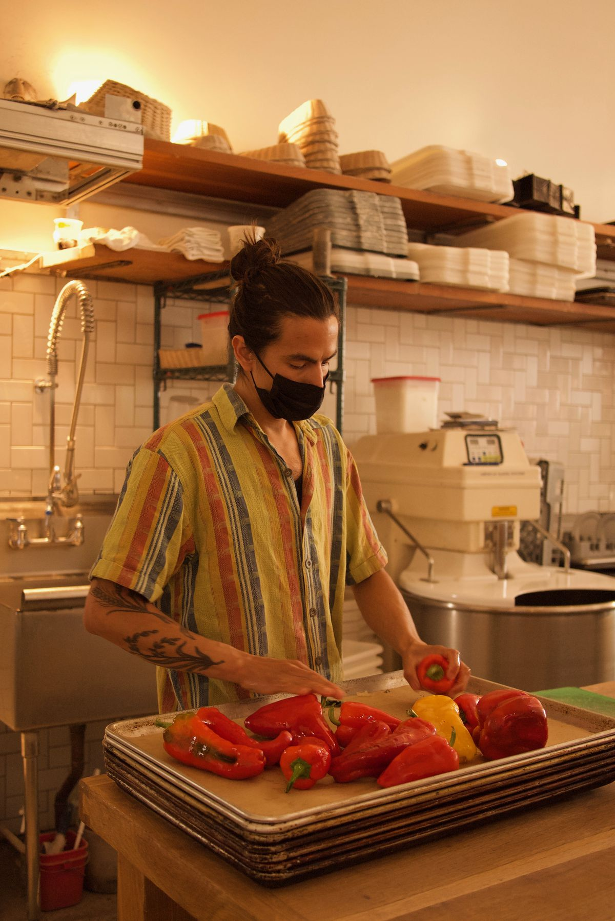 David X. Torres, wearing a mask, places whole red and yellow bell peppers on a sheet tray in a kitchen.