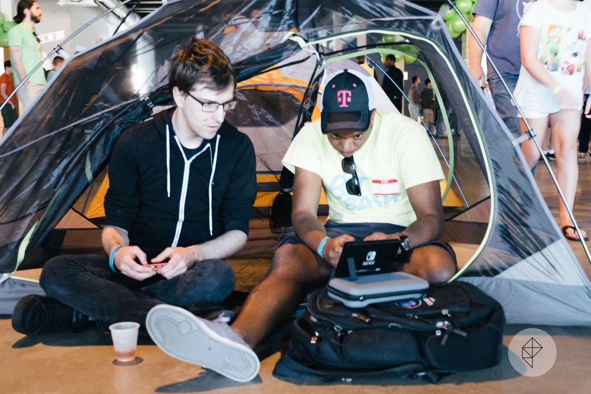 Two people play the Nintendo Switch console inside a nylon tent.