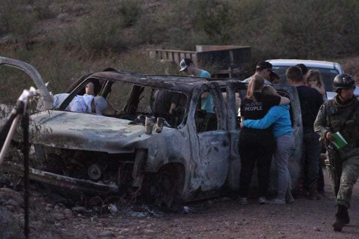 People on Tuesday, Nov. 5, 2019, gather around the burned-out remains of a vehicle that was being used by some members of the LeBaron family as they were driving in a convoy near the Sonora-Chihuahua border in Mexico. Mexican authorities say drug cartel gunmen ambushed multiple vehicles, including this one, slaughtering three women and six children.