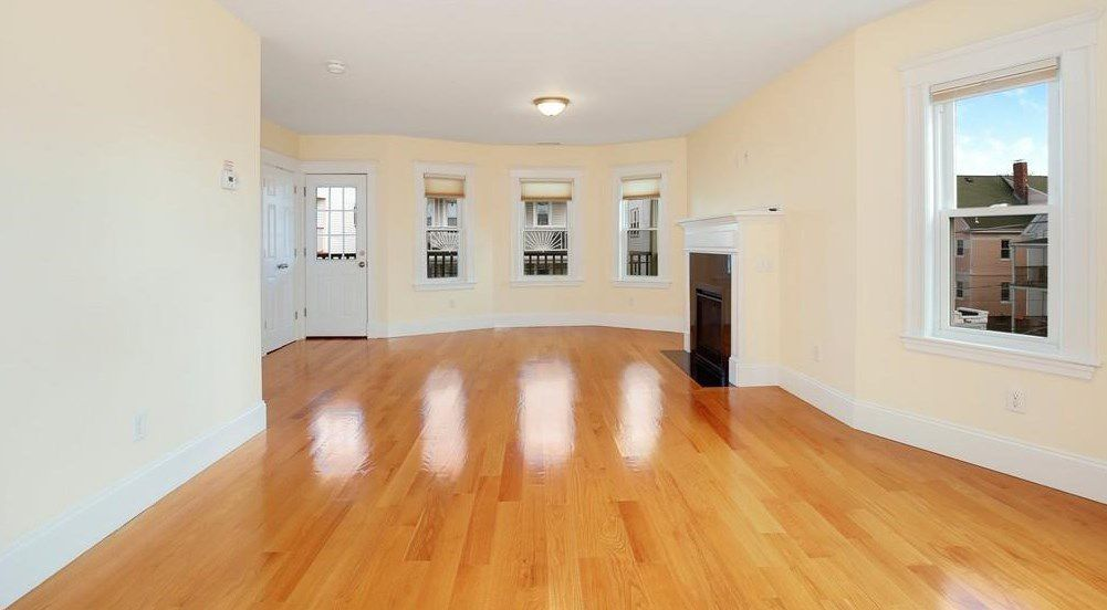 An empty living room with a bay window and a fireplace.