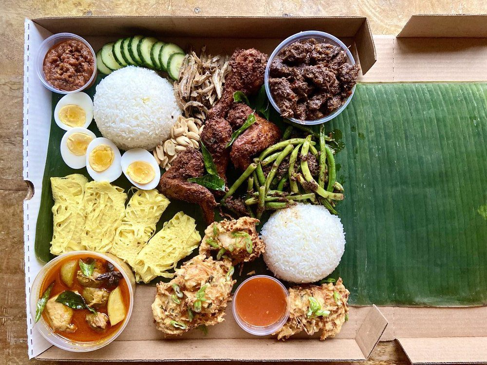A box of food including hardboiled eggs and other dishes artfully spread out on a banana leaf.