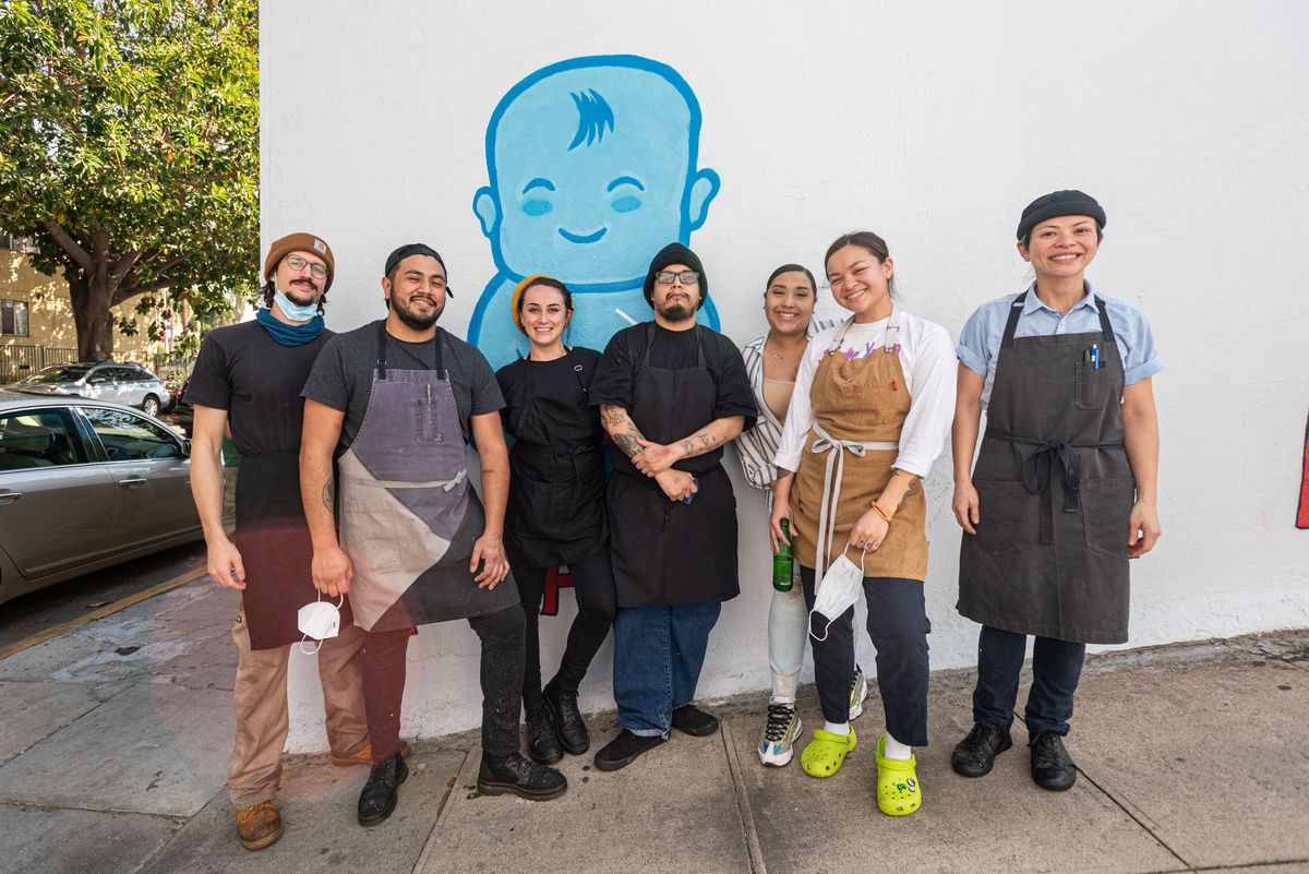Team picture of Uyen Le with her staff in front of the chubby baby mural.