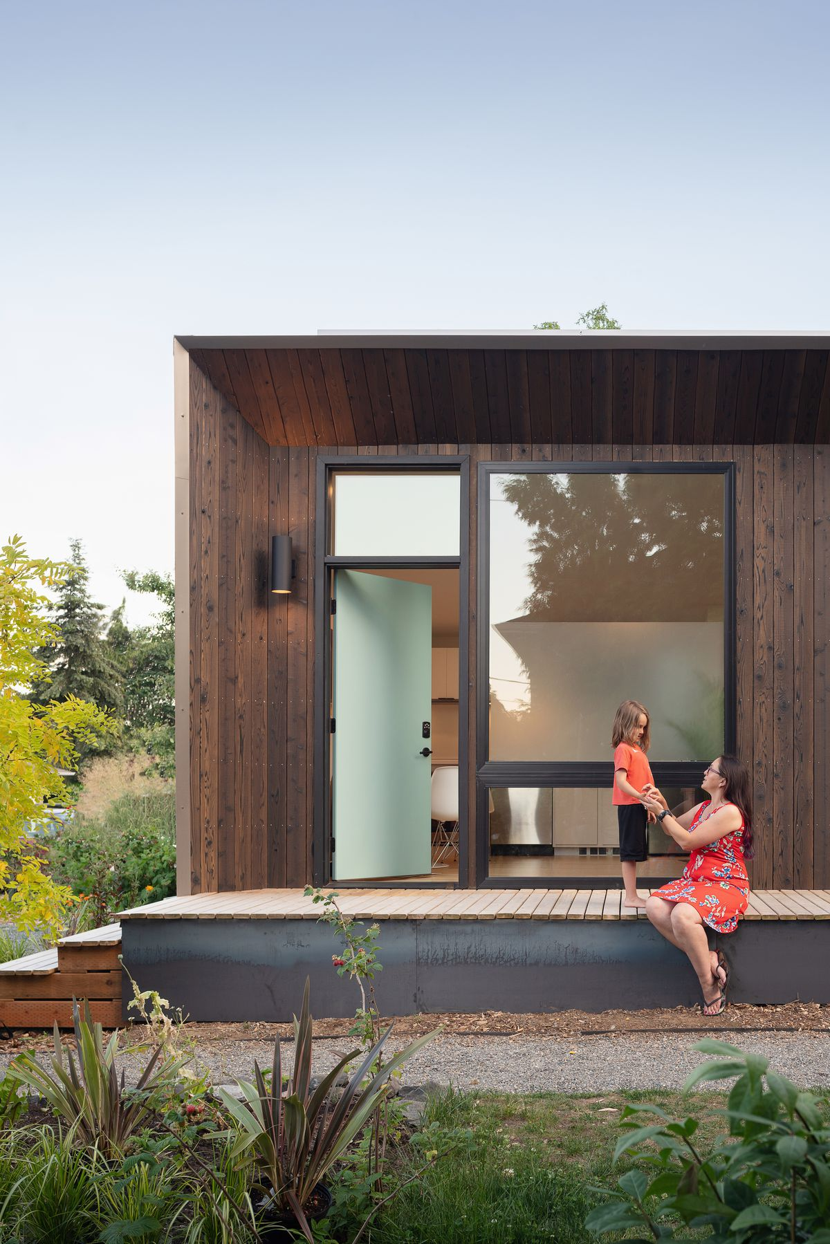 A woman and child interact on the front deck of a small, modern house.