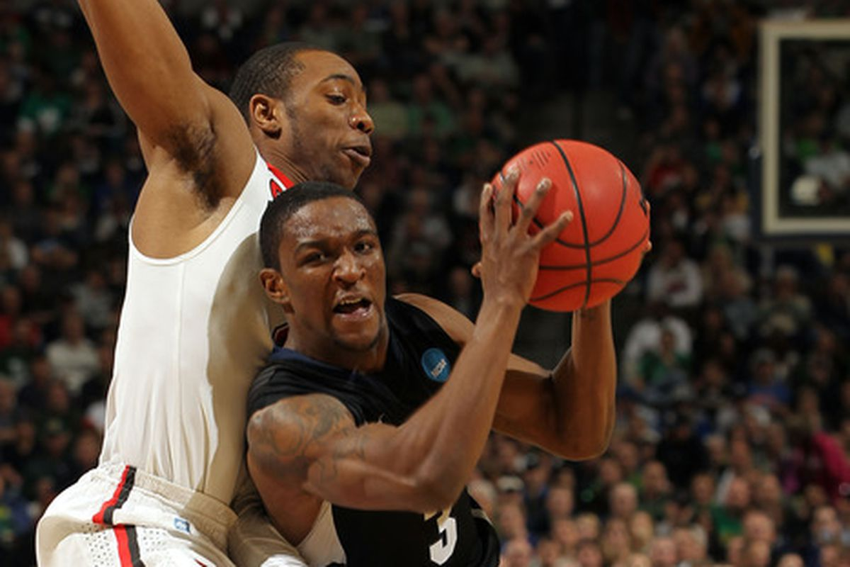 Packers CB Demetri Goodson (with ball) drives during a college basketball game in 2011.