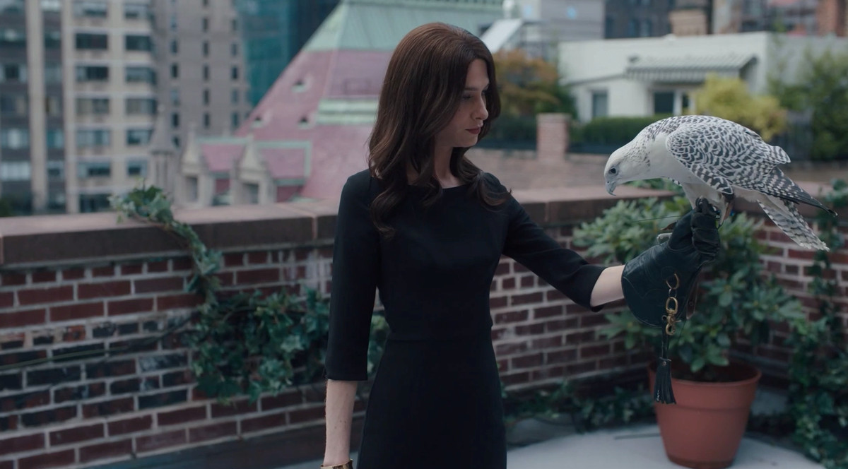 Taylor in a black dress and wig holding an eagle on their arm
