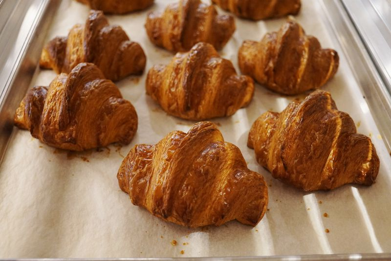 Golden brown croissants cooling on the rack.