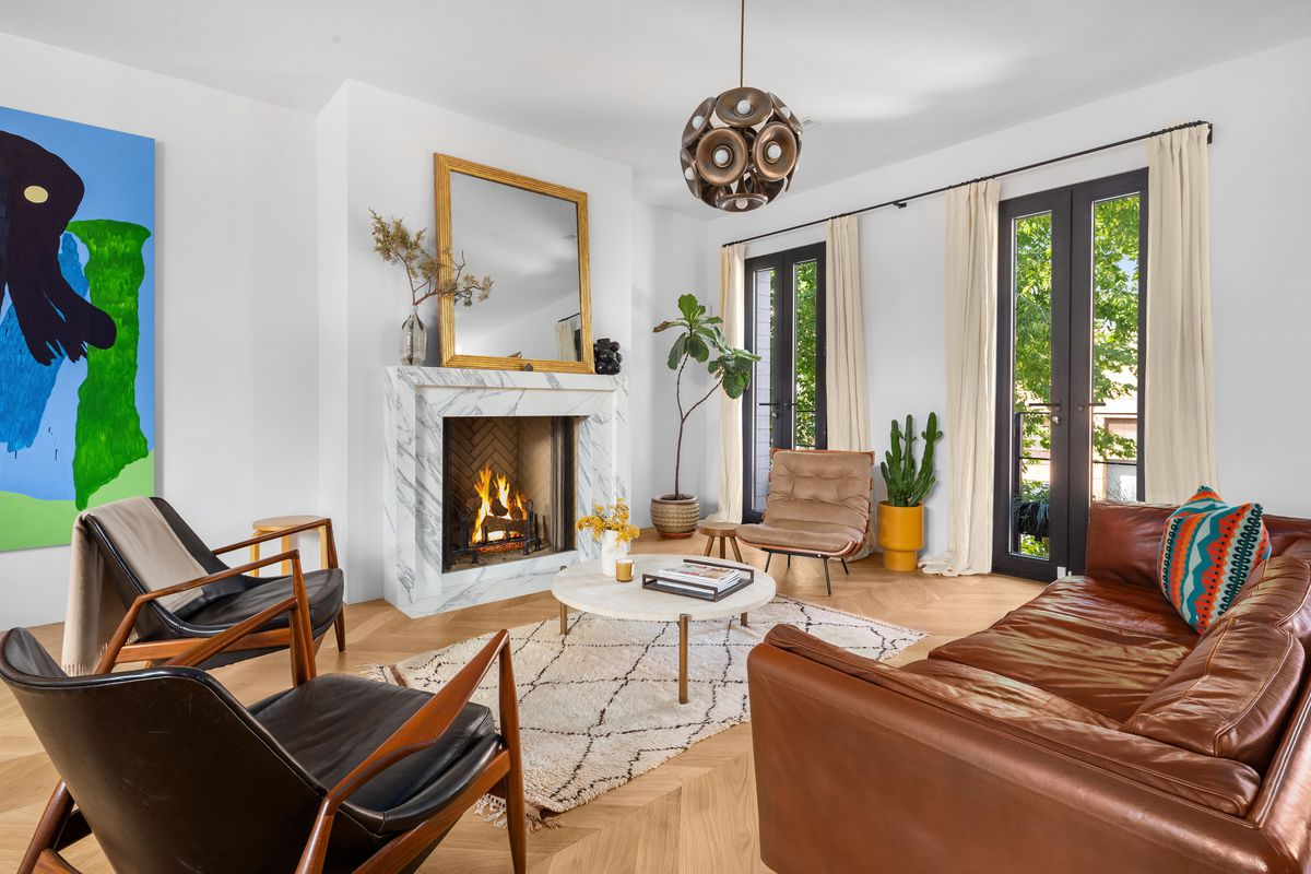 A living room with a marble fireplace mantel, large windows, a mirror with a gold frame, and a large chandelier. There is a brown leather couch and two black leather armchairs.
