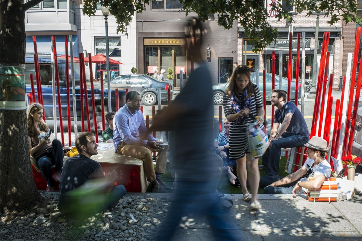 A group of people sits in a temporary mini-park installed in a street parking space in the middle of a city.