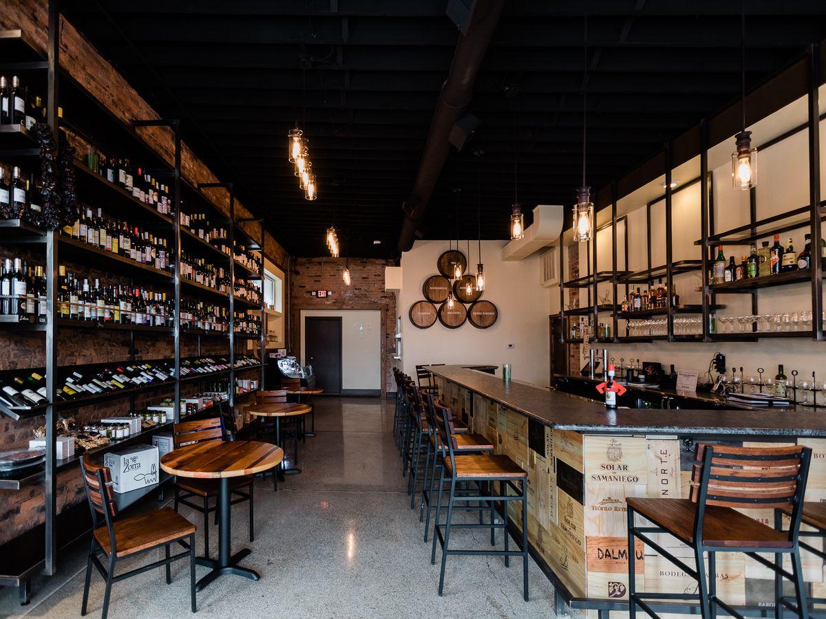 Barrels and wine racks line the walls surrounding the bar at Cata Vino.