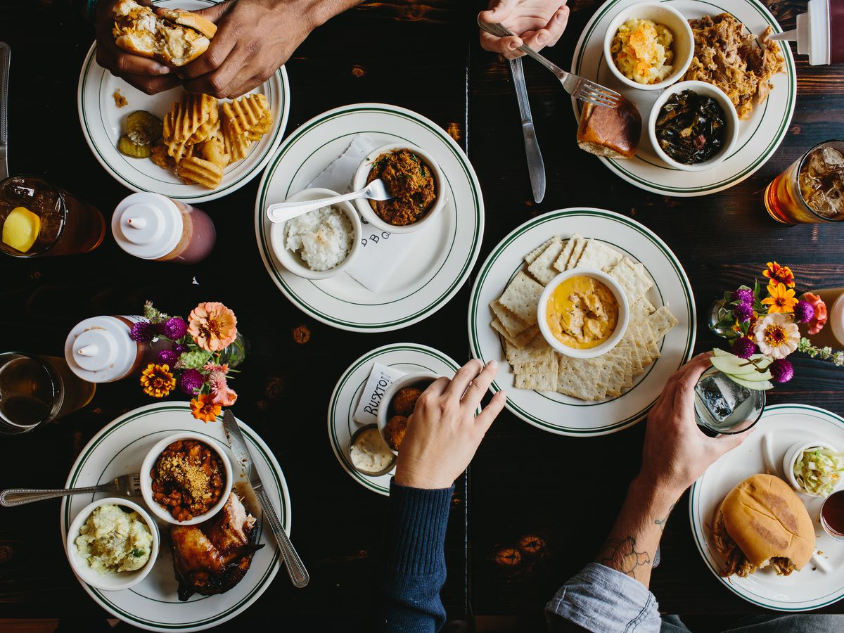 An overhead shot of a table packed with barbecue. Several hands grab at sandwiches, pulled pork, mac and cheese, beans, BBQ chicken, and more.
