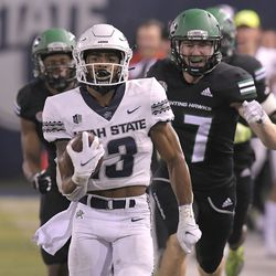 Utah State wide receiver Deven Thompkins (13) runs down the field for a 75-yard touchdown as North Dakota defensive back C.J. Siegel, left, and defensive back Hayden Galvin (17) defend during the second half of an NCAA college football game Friday, Sept. 10, 2021, in Logan, Utah.