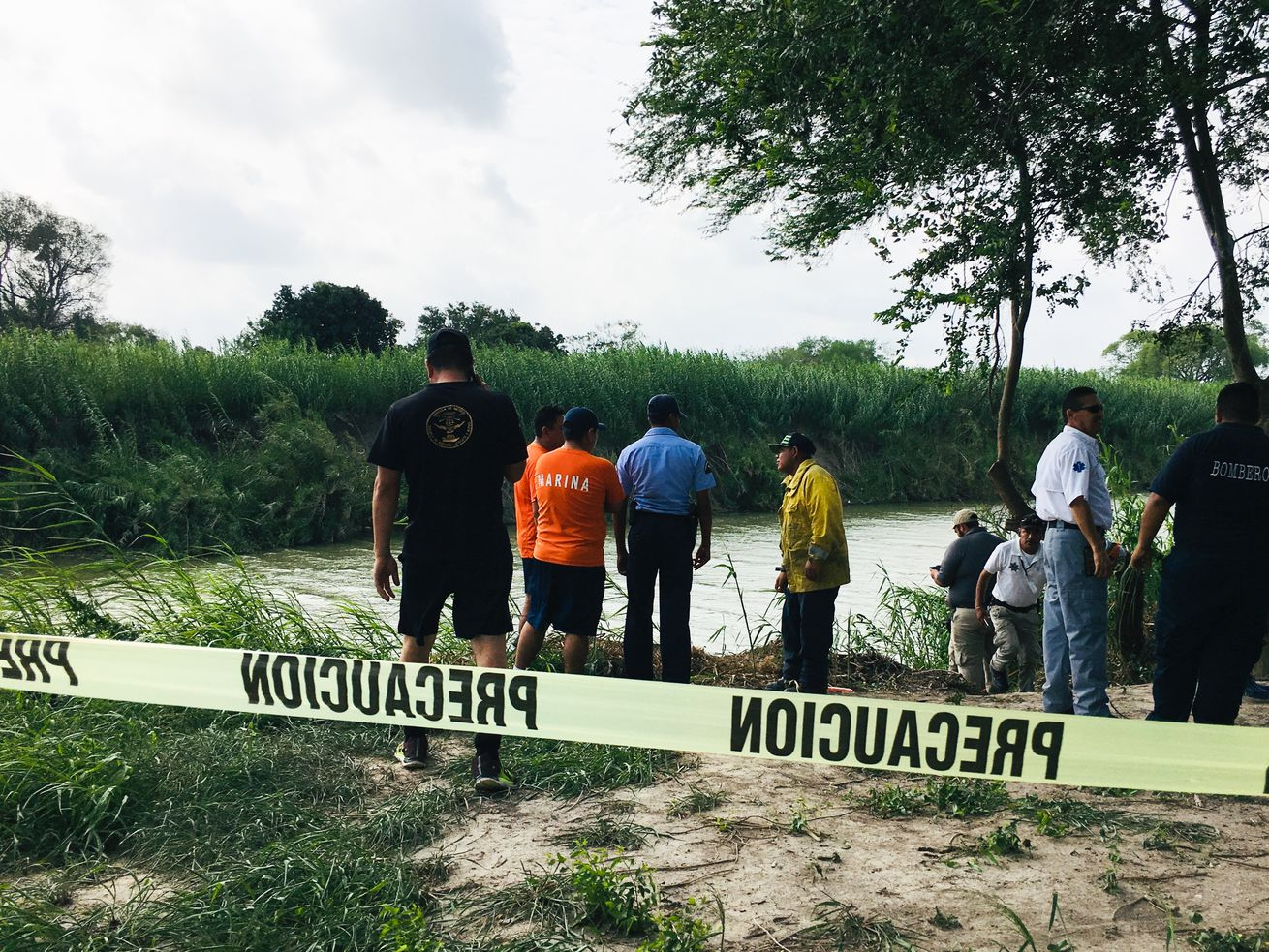Authorities stand behind yellow warning tape along the Rio Grande bank where the bodies of Salvadoran migrant Oscar Alberto Martínez Ramírez and his nearly 2-year-old daughter Valeria were found, in Matamoros, Mexico, on June 24, 2019, after they drowned trying to cross the river to Brownsville, Texas.