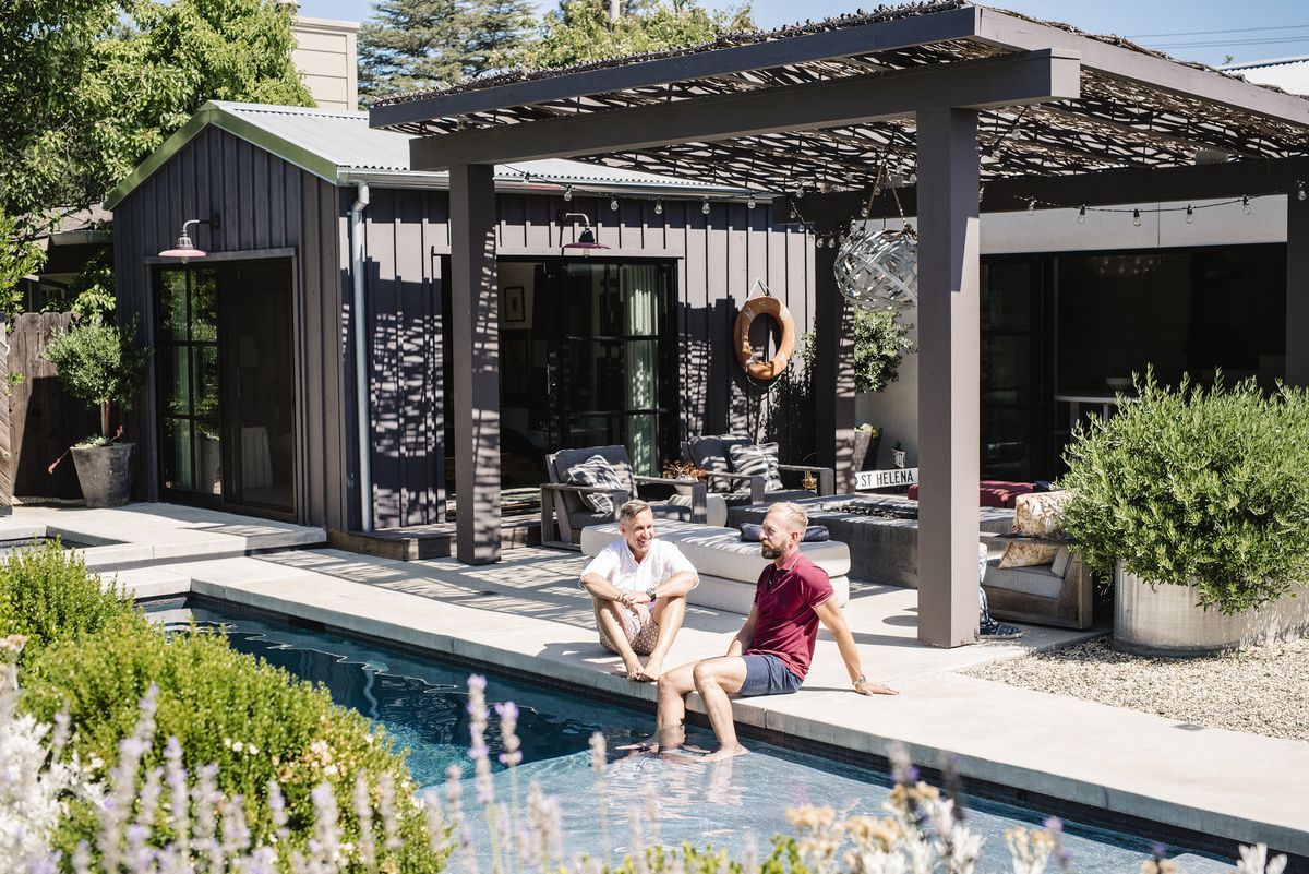 Two men sit by the side of a swimming pool. There is an outdoor seating area behind them with a couch, table, and arm chairs. A dark brown house is adjacent to the outdoor seating area.