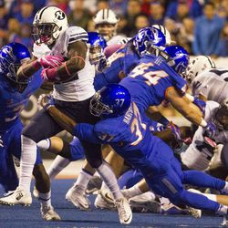 Brigham Young running back Squally Canada (22) carries Boise State safety Cameron Hartsfield (37) during the first half of an NCAA football game between Boise State and Brigham Young in Boise on Thursday, Oct. 20, 2016.