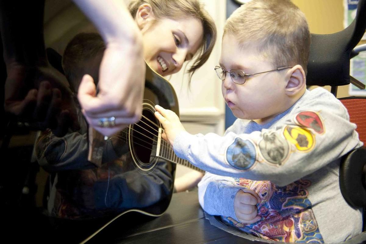 In this Feb. 23, 2012. Blake Roberts, then reaches out to strum the strings of music therapist Kristin Veteto's guitar during a session in  Columbia, Mo. Music therapy uses music to help individuals reach therapeutic goals in the physical, cognitive and s
