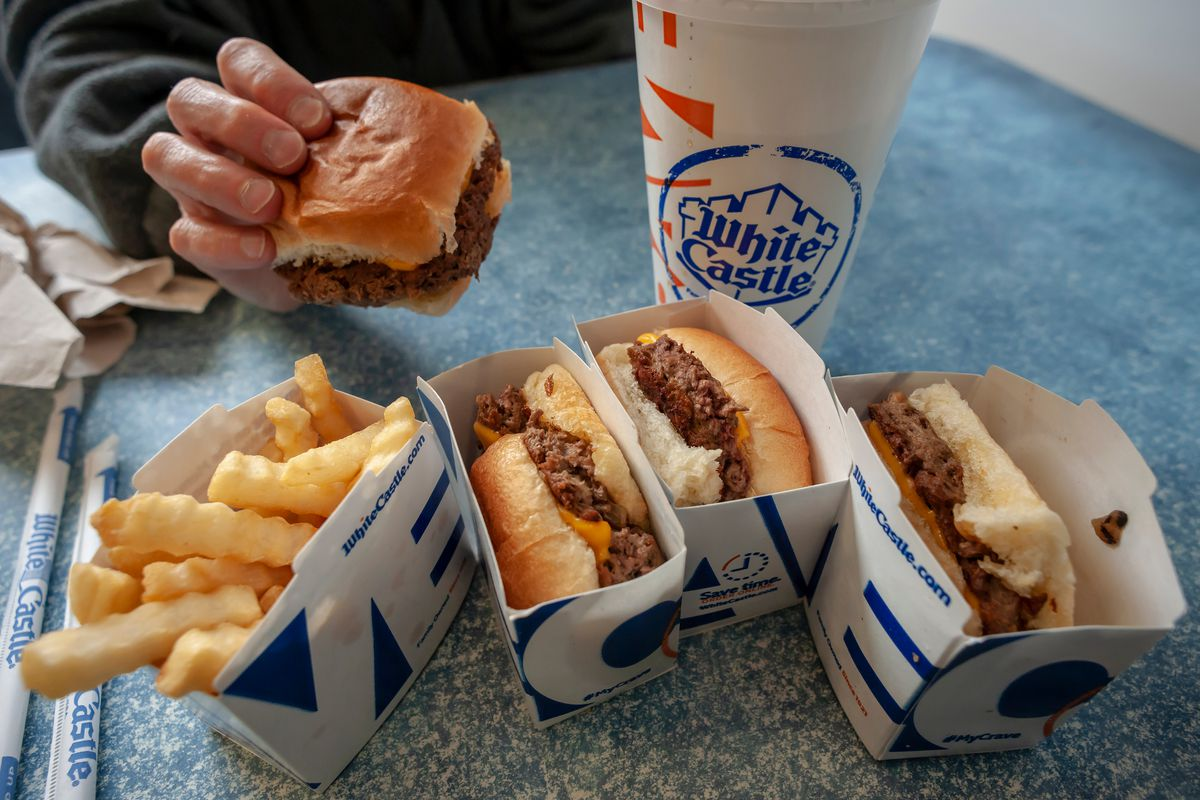 Hand holding White Castle slider, on a table with other White Castle food.