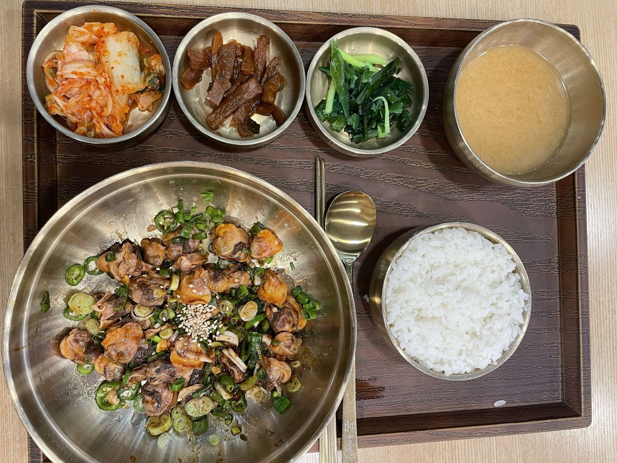 a bibimbap set served in copper bowls complete with kimchi, spinach, radish, and bean paste soup