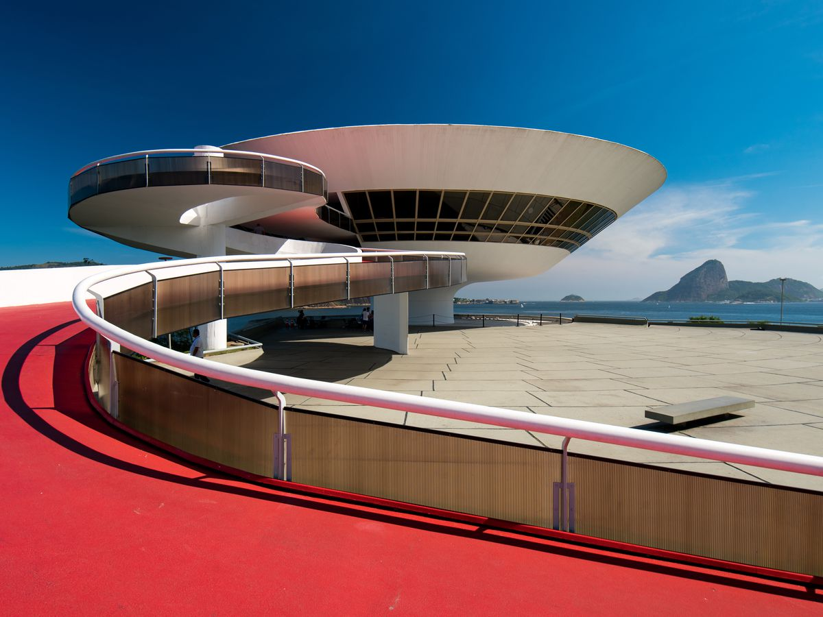 The exterior of the Niteroi Contemporary Art Museum. There is a red carpeted ramp leading up to a pedestal shaped building.