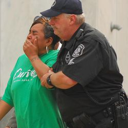 Ronda Thaxton, the mother of Klein Michael Thaxton is escorted by Pittsburgh Police Officer Ray Kain to the command center during the standoff atThree Gateway Center, Friday, Sept. 21, 2012. Klein Michael Thaxton, 22, held a businessman hostage inside the office building for more than five hours Friday, posting Facebook updates during the standoff, and surrendered to authorities without incident, police said.