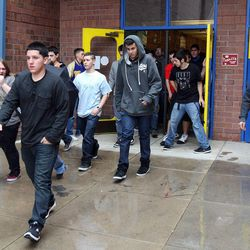 Taylorsville High School students walk out of school into the rain as they participate in an earthquake drill for The Great Utah ShakeOut, Tuesday, April 17, 2012.