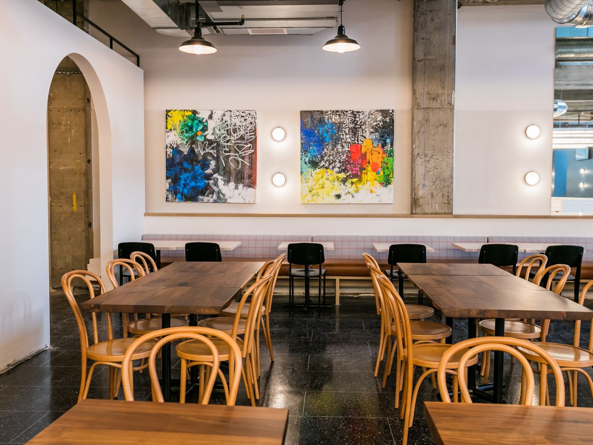 Communal are surrounded by white walls with rainbow colored paintings at Fort Street Galley.