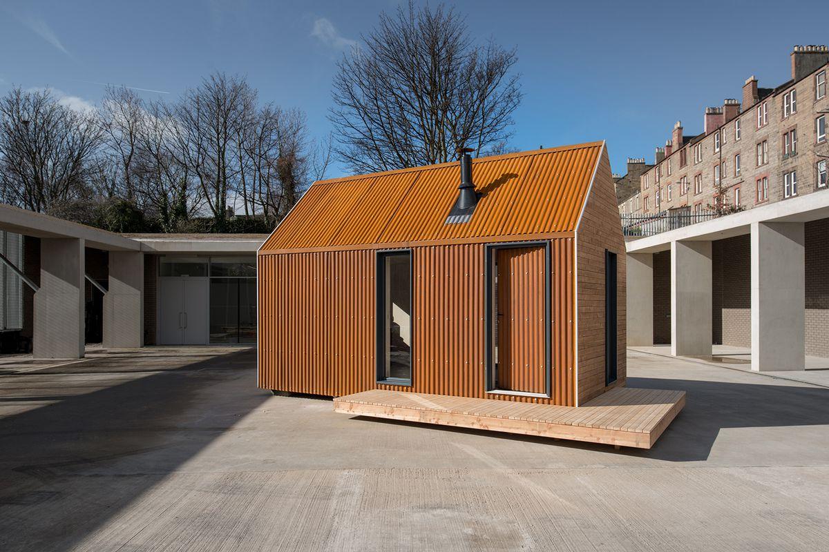 Small prefab cabin sitting in a courtyard