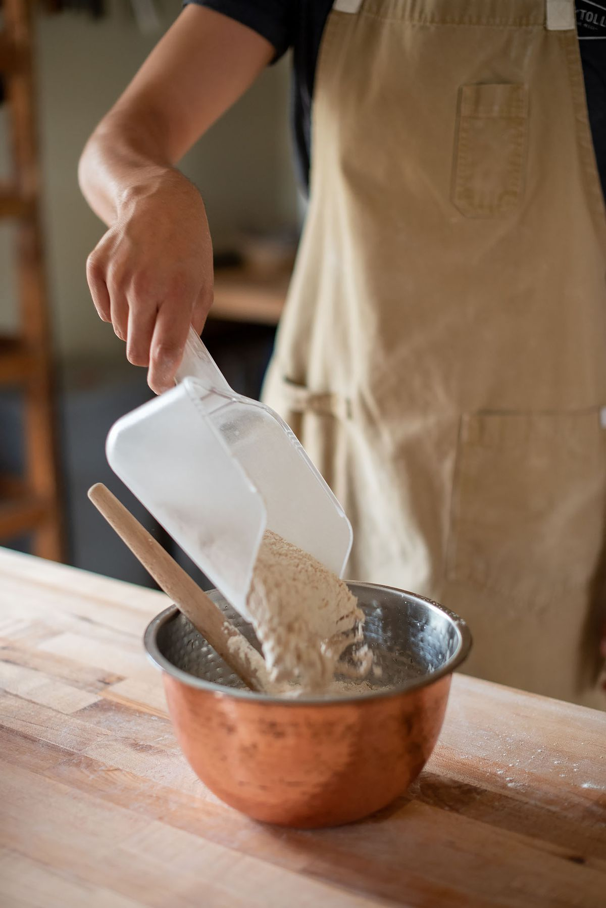 Readying flour at a home bakery, using a copper bowl.
