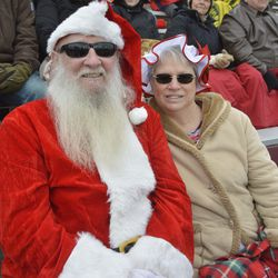 Fans dressed as Santa and Mrs. Claus pose for the camera during the second quarter.