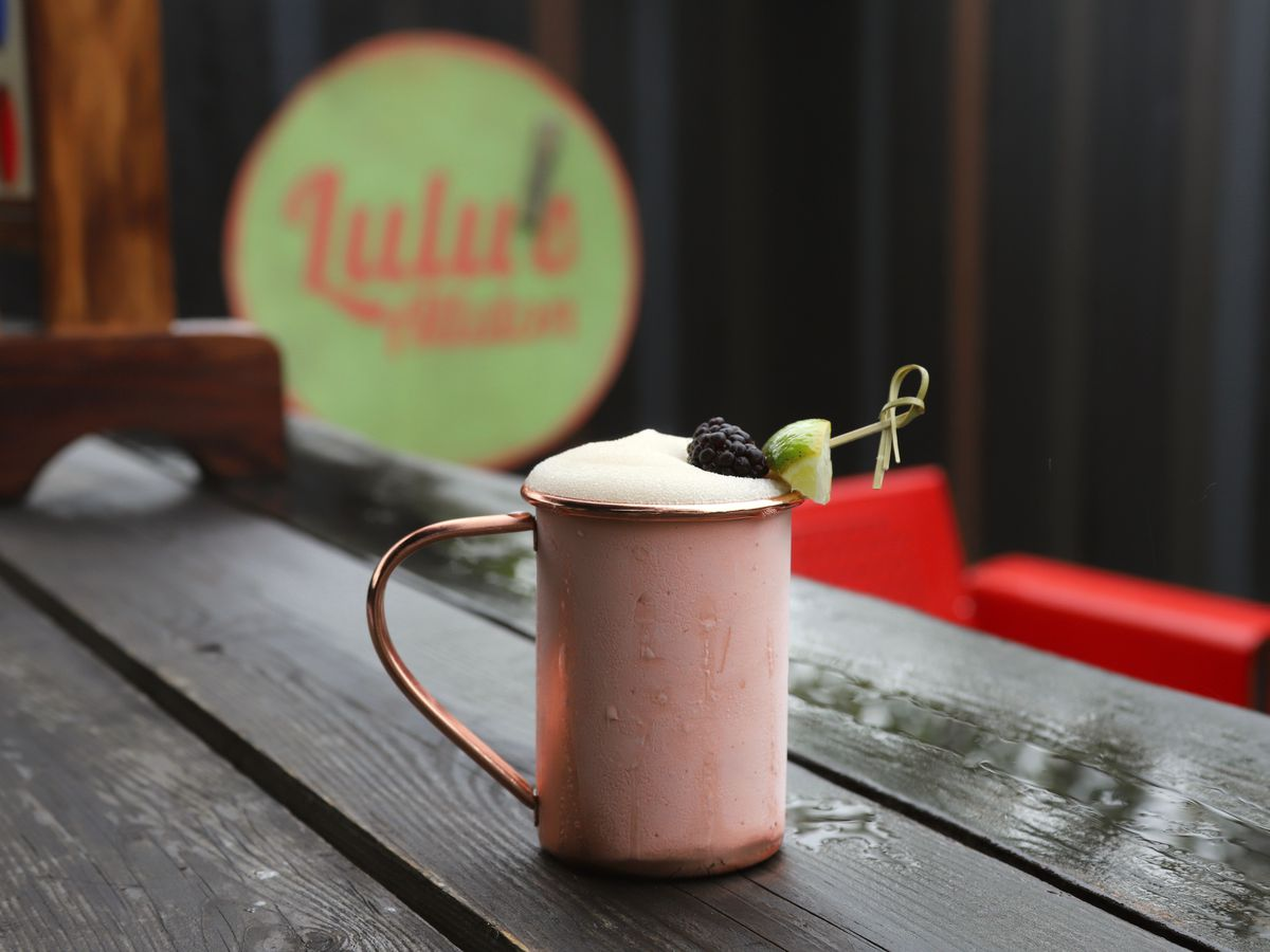 A frozen cocktail served in a copper mule mug, garnished with a blackberry, sits on a picnic table on a restaurant patio. Lulu's Allston signage is visible in the back.