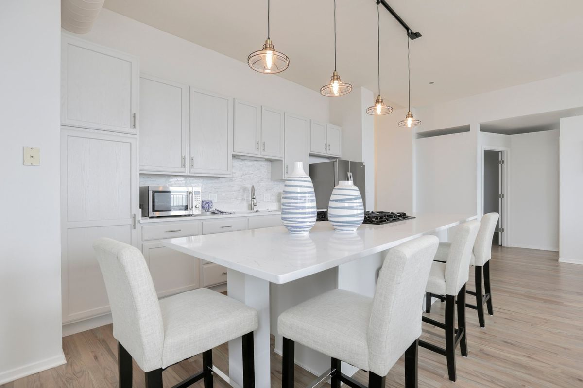 A kitchen with white cabinets, white stone counters, four pendant lights, and four high-back stools.