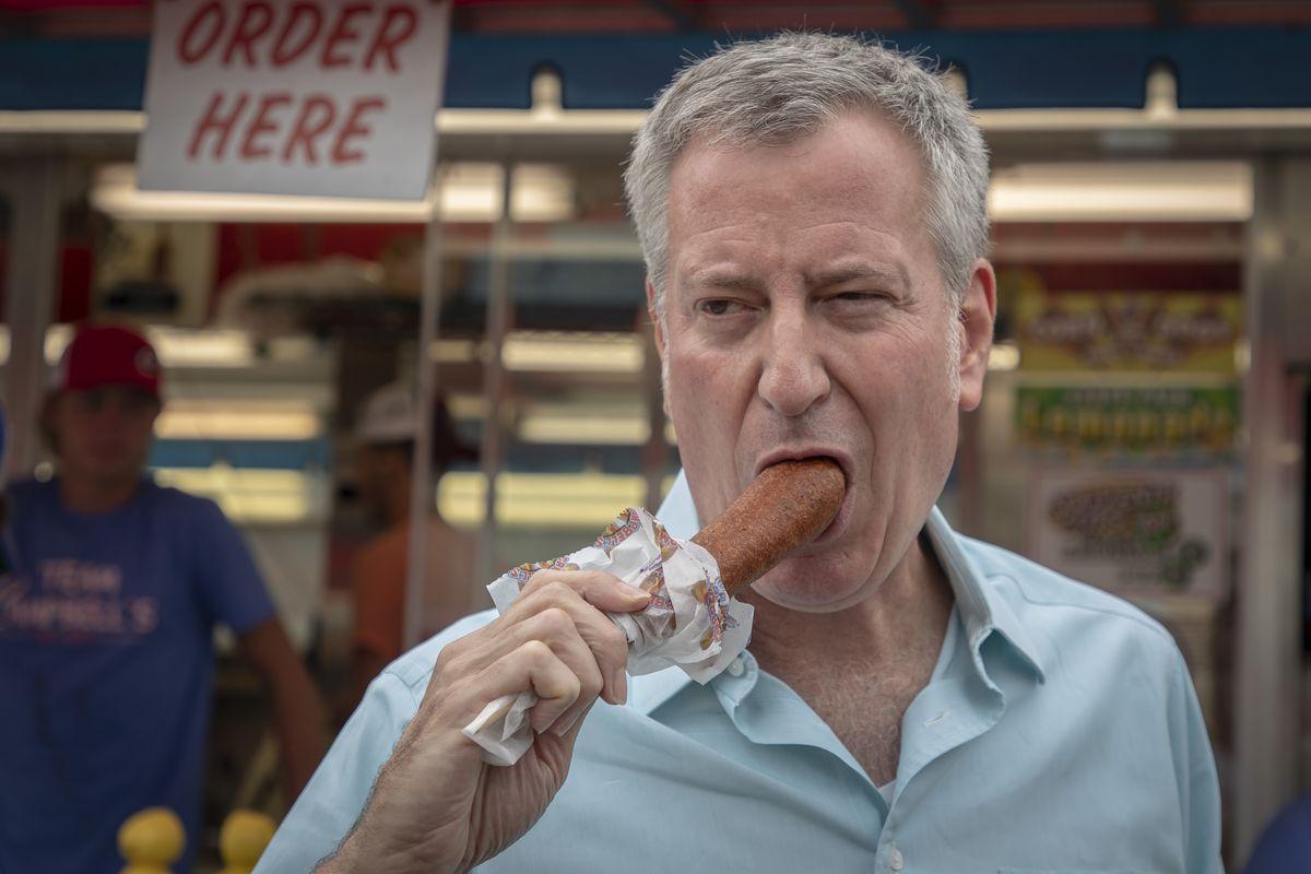 New York City Mayor Bill de Blasio bites into a corndog