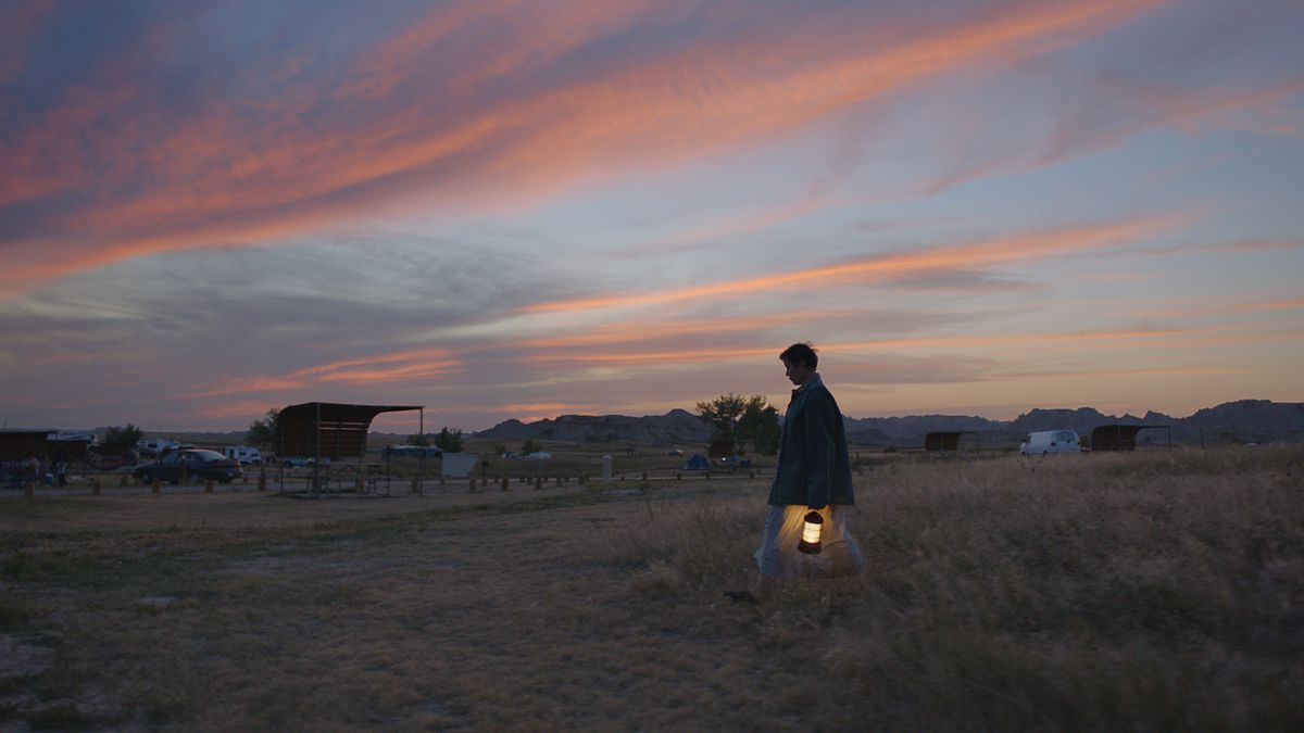 A woman carrying a lantern walks across a field at sunset.