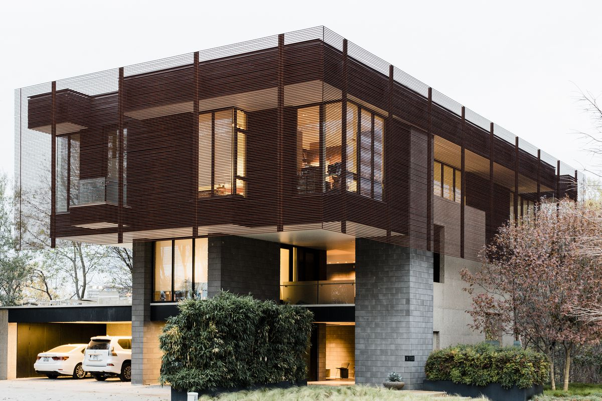 The house has a larger upper story that seems to hover over the more slender lower levels.