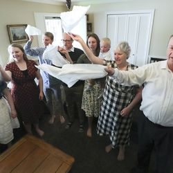 Ron and Wendy Van Tienderen, right, participate in the Hosanna Shout as they watch the Sunday morning session of the 190th Annual General Conference of The Church of Jesus Christ of Latter-day Saints with their children at their home in Millcreek on Sunday, April 5, 2020.