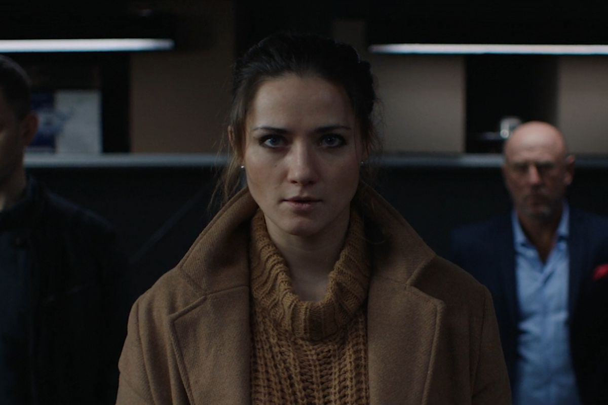 a serious-looking woman in a sweater is flanked by two angry-looking men in She Sees Red