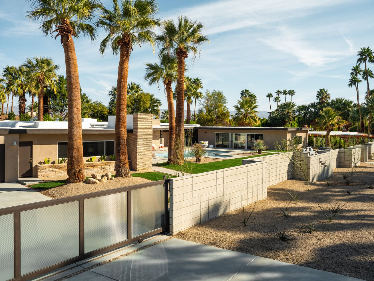 An external view of a ranch midcentury modern house, with an automatic gate, brick wall, and palm trees around.