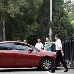 Chinese plain clothes security personnel stop a man from ramming his car against the gate of the Japanese embassy in Beijing, China Tuesday, Sept. 11, 2012. Chinese government ships are patrolling near contested East China Sea islands in a show of anger after Tokyo moved to assert its control in the area. Beijing warned Monday that Japan would suffer unspecified consequences if Tokyo purchased the islands from private owners, as it formally did Tuesday.