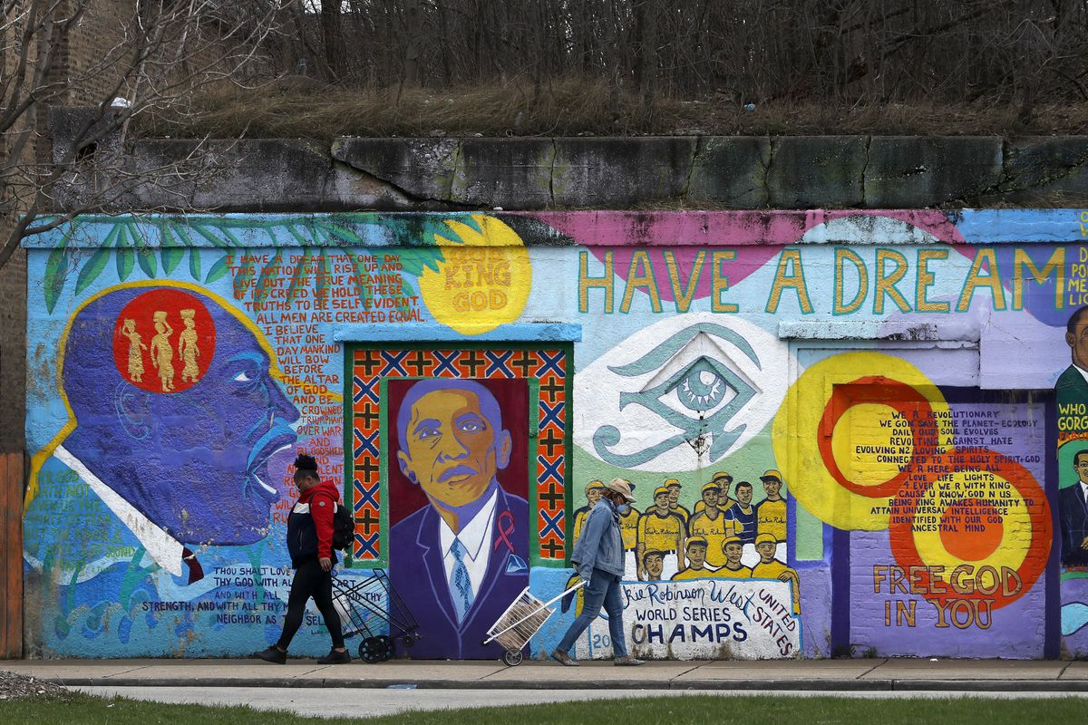 Two women walk past a mural on the South Side. Black Chicagoans are far more likely to contract and die from the coronavirus.