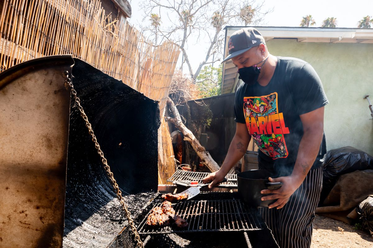 A man wearing a black face mask moves a piece of chicken on top of the hot grill