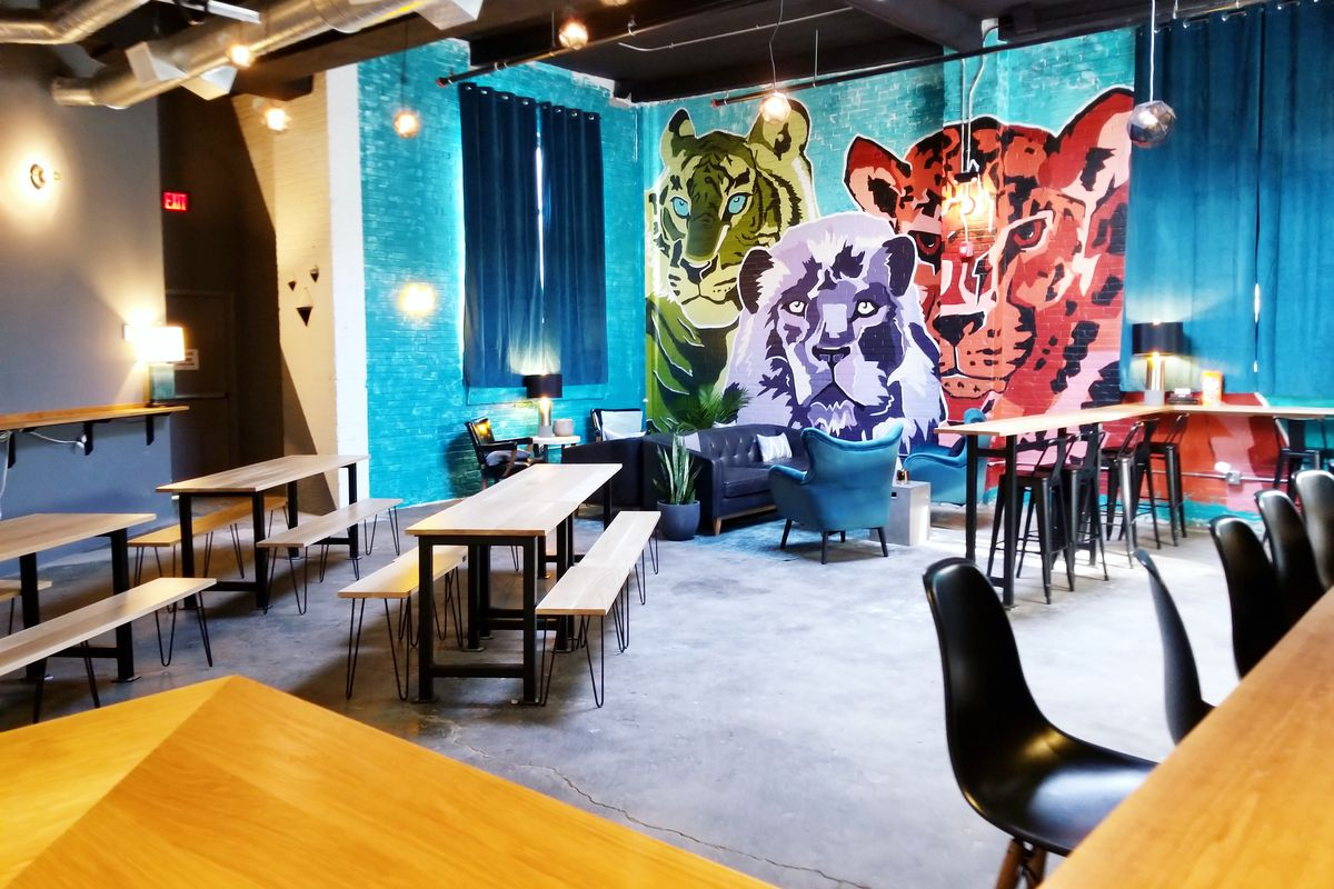 Wide view of a taproom with a mural of big, wild cats, bench seating, and bar seating