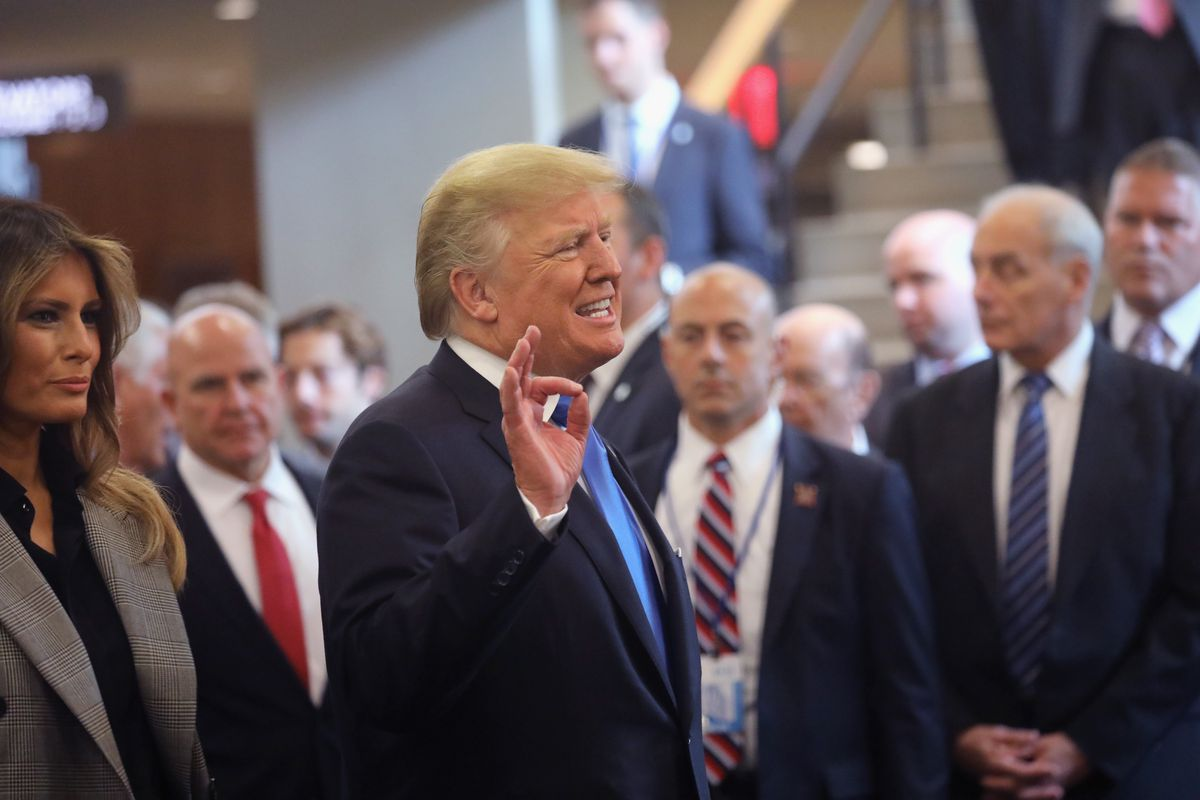 """President Donald Trump in a crowd at the United Nations, making an """"O.K."""" symbol with his right hand"""