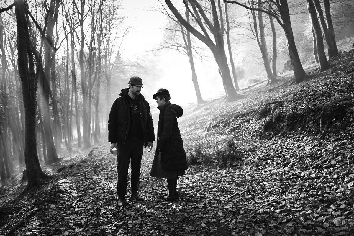 In a black-and-white, slightly tilted image, the director and star of Gretel and Hansel, both in puffy black coats, stand in a stark forest lined with fallen leaves.