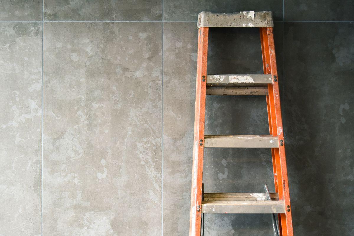 Orange, metal ladder leaning on wall.