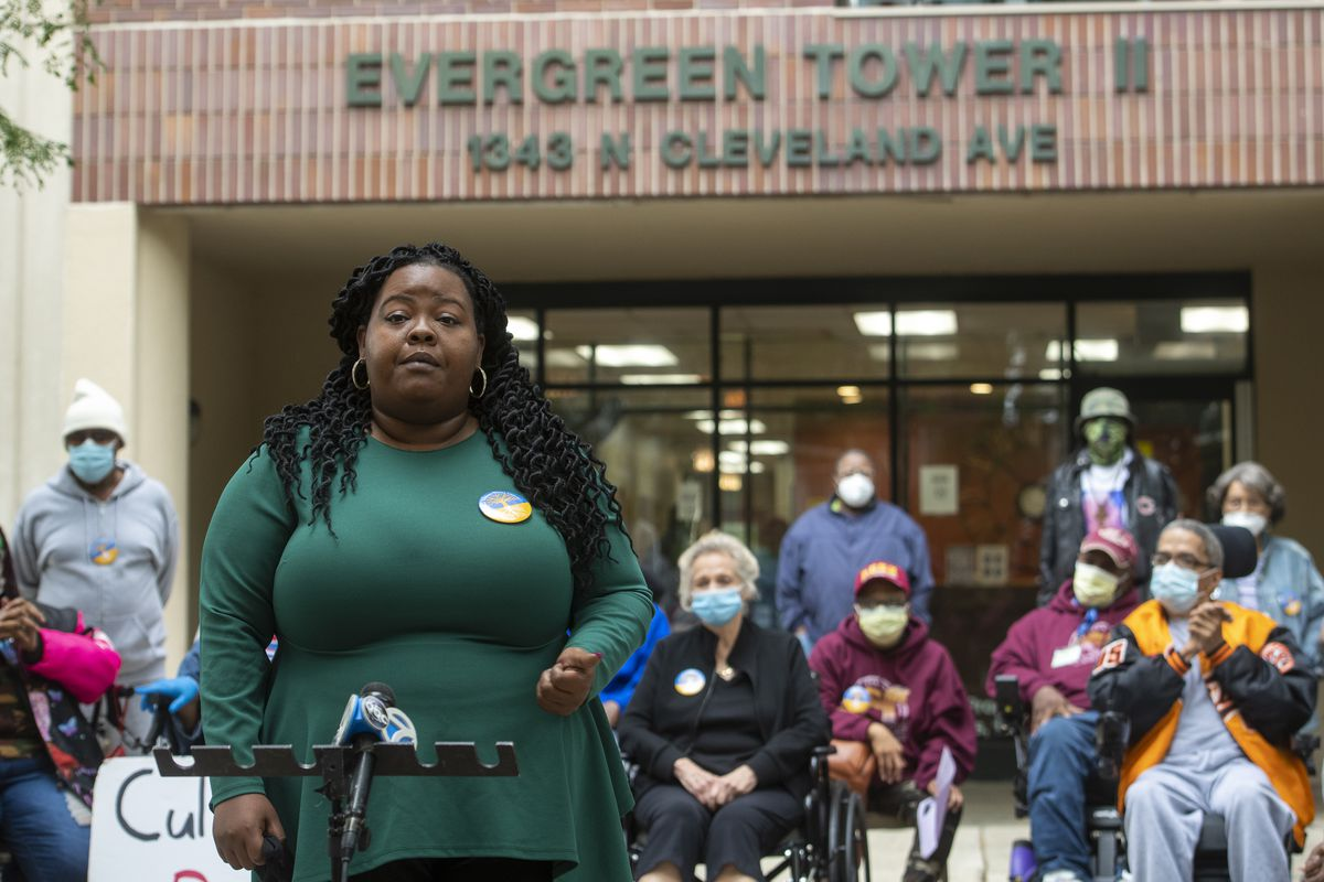 State Rep. Lakesia Collins speaks Wednesday outside Evergreen Tower II demanding that the owner of the building invest more for residents' safety.