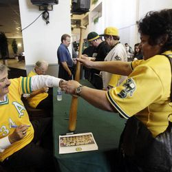 Former Oakland Athletics pitcher Rollie Fingers signs a bat for a fan during an appearance by the club's 1972 World Series championship baseball team on Friday, April 20, 2012, in Oakland, Calif.