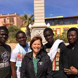 Sister Anita Herway, an LDS service missionary in Italy assisting with refugee aid and projects, visits with four refugees in Lampedusa, Italy.