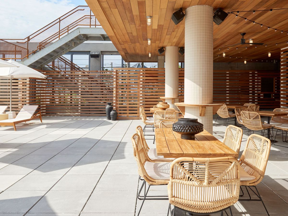 Several sets of light wooden furniture sit on a pool deck outdoors
