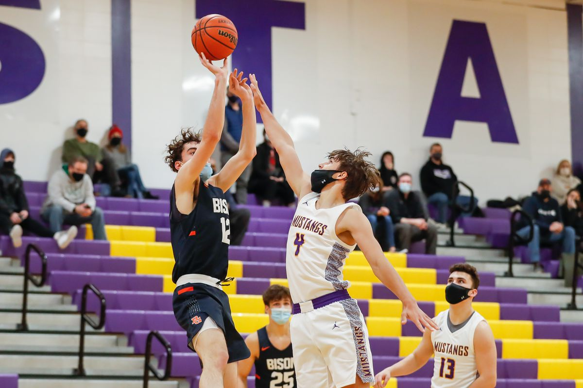 Buffalo Grove's Kam Craft (12) attempts to shoot the ball over Rolling Meadows' Daniel Sobkowicz (4).